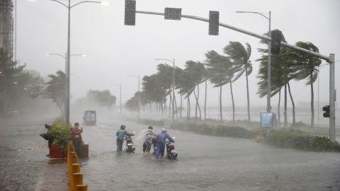 Motorists push their motor bikes through a flooded street in Manila on September 15.
