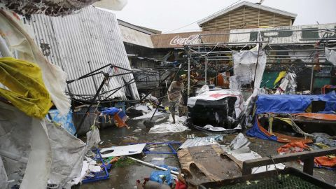 Residents walk along destroyed stalls at a public market due to strong winds as Typhoon Mangkhut barreled across Tuguegrao city in Cagayan province, northeastern Philippines on Saturday, Sept. 15, 2018. The typhoon slammed into the Philippines northeastern coast early Saturday, it's ferocious winds and blinding rain ripping off tin roof sheets and knocking out power, and plowed through the agricultural region at the start of the onslaught. (AP Photo/Aaron Favila)