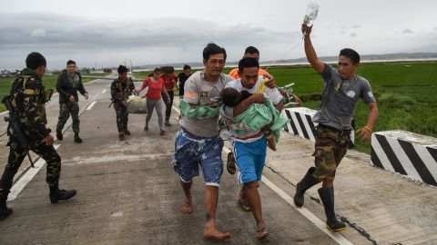 Philippine soldiers help a man with a sick child after fallen electric poles blocked an ambulance transporting them in Baggao, a town north of Manila, on September 15.