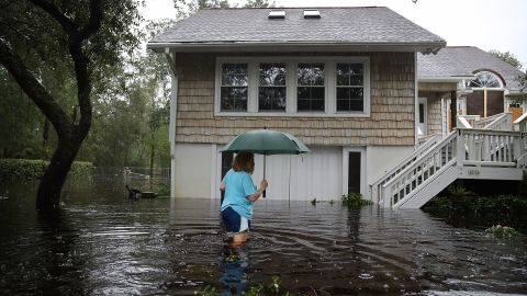 Kim Adams wades through floodwaters surrounding her home in Southport, North Carolina, on September 15.