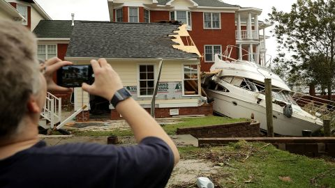 A neighbor takes photos of a boat smashed against a car garage near the Neuse River in New Bern on Saturday.