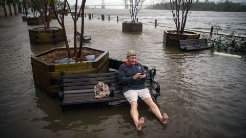 Ray Baca of Wilmington, North Carolina, checks his phone as he sits on a bench.