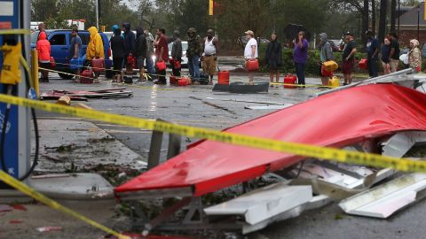 People wait in line to fill gas cans at a gas station that was damaged when Florence hit Wilmington, North Carolina, on Saturday.