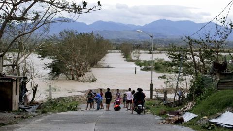 Residents stand by a flooded road in Tuguegarao city in northeastern Philippines, on Saturday, September 15.