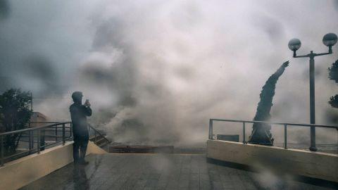 A man takes a photograph as waves crash over a promenade in Hong Kong, on Sunday.