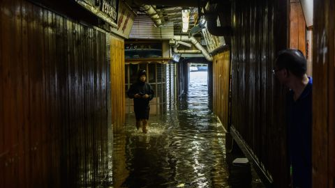 Villagers look down an alleyway filled with seawater in Lei Yu Mun on Sunday.