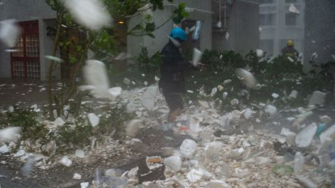 A photojournalist walks amongst plastic debris blown by strong winds in the residential district of Heng Fa Chuen during Super Typhoon Mangkhut in Hong Kong on September 16, 2018. (Photo by Philip FONG / AFP)        (Photo credit should read PHILIP FONG/AFP/Getty Images)
