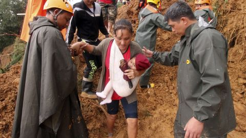 Rescuers assist a mother and her child as they evacuate to safer grounds following landslides in the Benguet province in northern Philippines on Sunday.