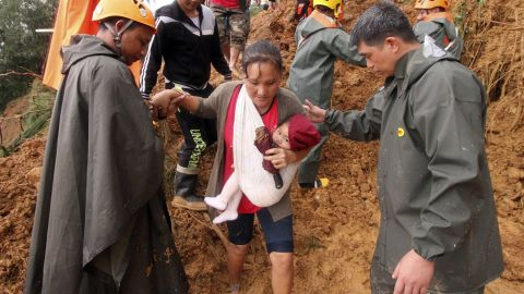Rescuers assist a mother and her child after the deadly landslide in the Philippines.