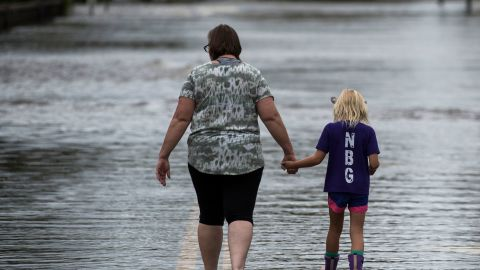 A woman and a young girl walk down a flooded road in Pollocksville on September 16.