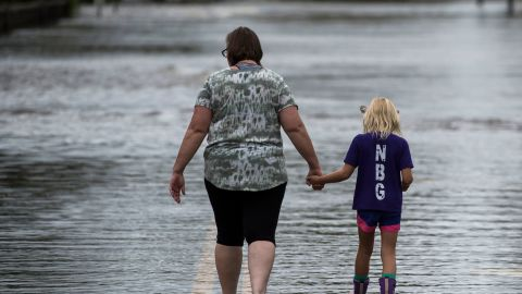 A woman holds a young girl's hand as they walk down a road flooded by Hurricane Florence in Pollocksville, North Carolina, on September 16, 2018. - Catastrophic floods raised the threat of dam breaks and landslides across the southeastern United States, prolonging the agony caused by a killer hurricane that has left more than a dozen people dead and billions of dollars in damage. (Photo by Andrew CABALLERO-REYNOLDS / AFP)        (Photo credit should read ANDREW CABALLERO-REYNOLDS/AFP/Getty Images)
