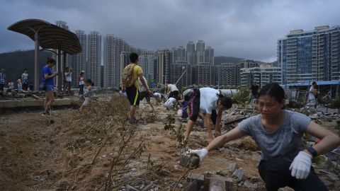 People clean debris from Typhoon Mangkhut on the waterfront in Hong Kong, Monday, Sept. 17, 2018. Hong Kong and southern China hunkered down as strong winds and heavy rain from Typhoon Mangkhut lash the densely populated coast. The biggest storm of the year left at least 28 dead from landslides and drownings as it sliced through the northern Philippines.