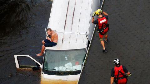 Pollocksville resident Willie Schubert cradles his dog, Lucky, atop a stranded van as they await help from the US Coast Guard on September 17.