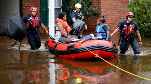 Rescue personnel help people evacuate a flooded area in Spring Lake, North Carolina.