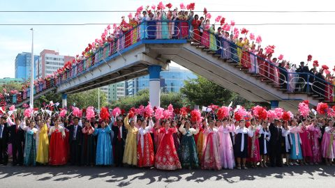 North Koreans wave bouquets and flags as they watch the two leaders' parade in Pyongyang on September 18.