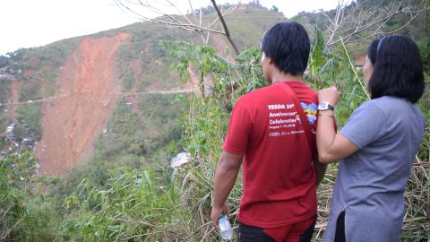 People look at the landslide site in Itogon as rescuers used shovels and their bare hands to claw through mounds of rocky soil.