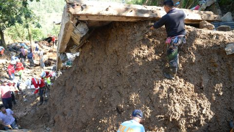 Rescuers dig at a landslide site where dozens of residents are believed to have been buried.