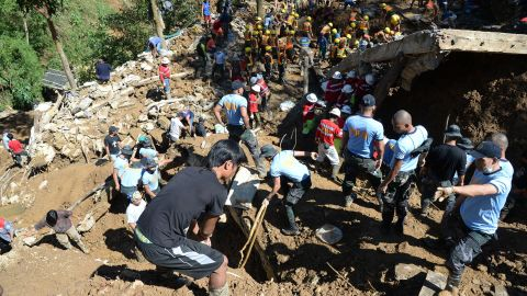 Rescuers dig on the remains of a building which was swept away by the landslide.