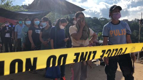 Family members wait to view recovered bodies from the landslide, hoping to identify their loved ones.