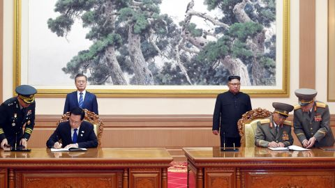"""South Korean Defense Minister Song Young-moo, second from left, and his North Korean counterpart No Kwang Chol sign a military agreement, vowing to """"cease all hostile acts against each other."""""""