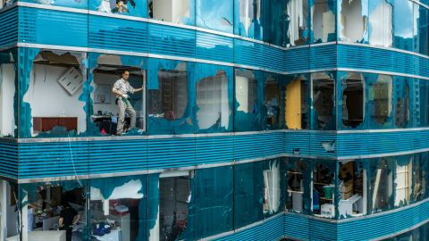 A man looks out of a damaged building in Hong Kong after Typhoon Manghkut.