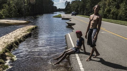 A woman in Currie, North Carolina, sits on a damaged road surrounded by floodwaters on Tuesday, September 18.