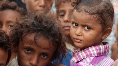 Displaced Yemeni children look on in a camp set up for people who fled the battle areas east of the port city of Hodeidah.