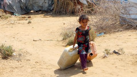 A displaced Yemeni girl from Hodeidah carries water containers at a makeshift camp in a village in the northern district of Abs.