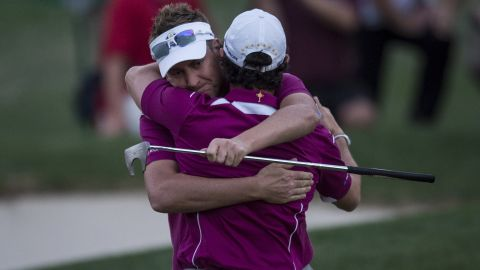 Ian Poulter and partner Rory McIlroy embrace after winning their match in 2012.
