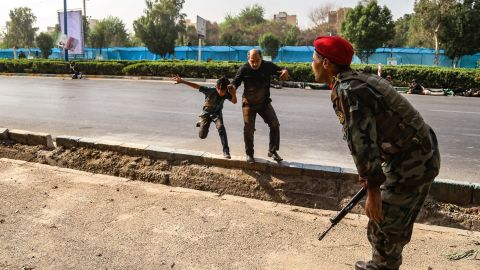 A man and a boy run to escape from the barage of gunfire in Ahvaz.