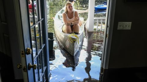 Maura Walbourne sits in the front of a canoe as she looks inside her flooded home in Conway, South Carolina, on Sunday, September 23.