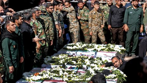 Iranian military members mourn over the bodies during a public funeral ceremony for those killed during an attack on a military parade on the weekend, in the southwestern Iranian city of Ahvaz on September 24, 2018. - Four militants attacked a Saturday parade marking the start of the 1980-1988 Iran-Iraq war, spraying the crowd with gunfire and killing 24 people. (Photo by ATTA KENARE / AFP)        (Photo credit should read ATTA KENARE/AFP/Getty Images)