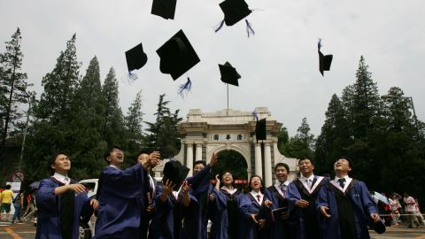 Students throw their mortar boards into the air as they graduate during a ceremony held at the Tsinghua University on July 18, 2007 in Beijing, China.
