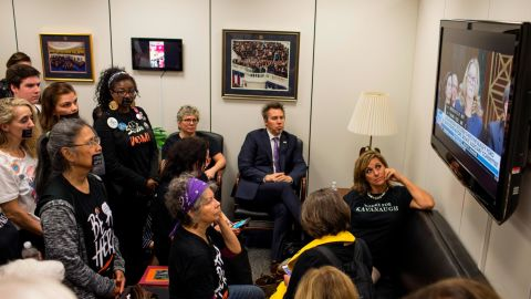 In this September 27, 2018, file photo, Protesters and supporters of Supreme Court Nominee Brett Kavanaugh watch Christine Blasey Ford's testimony from Sen. Chuck Grassley's office in Washington.
