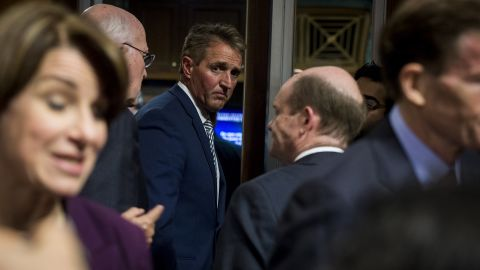 Sen. Jeff Flake  exits the Senate Judiciary Committee meeting about the Supreme Court nominee Brett Kavanaugh, Sept. 28, 2018.