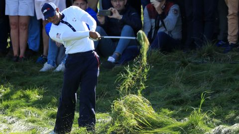 Team USA's Woods hits from the rough during a Saturday foursomes match.