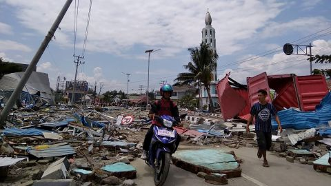 Palu residents make their way along a street full of debris on September 29. Palu is a coastal city of about 350,000.
