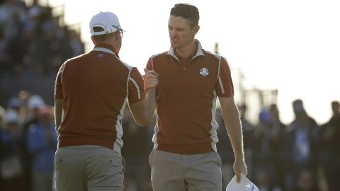 Europe's Justin Rose, right, celebrates with teammate Henrik Stenson on the 17th green after winning a foursomes match Saturday.