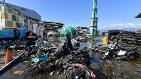 A resident sifts through debris past the rubble of a mosque in Palu, Indonesia's Central Sulawesi following the September 28 earthquake and tsunami.