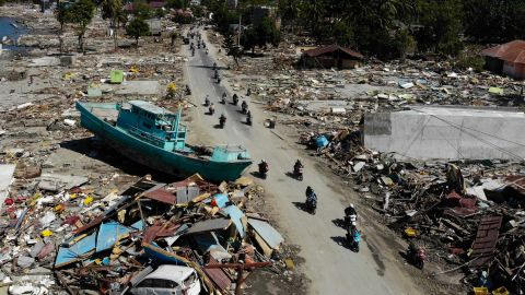People ride past a boat and other debris in Palu on October 1.