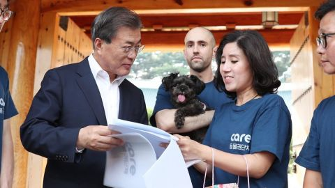 South Korean President Moon Jae-in goes over paperwork to adopt a new 'first dog,' Tory, from Care Korea.