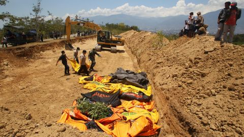 Bodies are carried to a mass grave in Palu's Balaroa village on October 1.