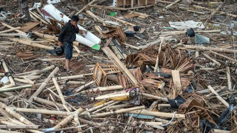 PALU, INDONESIA - OCTOBER 01: A man covers his nose as he walks through the rubble and debris of a building that was destroyed by a tsunami, on October 01, 2018 in Palu, Indonesia. Over 844 people have been confirmed dead after a tsunami triggered by a magnitude 7.5 earthquake slammed into Indonesia's coastline on the island of Sulawesi, causing thousands of homes to collapse, along with hospitals, hotels and shopping centers. Emergency services fear that the death toll could rise into the thousands as rescue teams made contact with the nearby cities of Donggala and Mamuju and strong aftershocks continue to rock the city. (Photo by Carl Court/Getty Images)