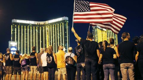 People form a human chain around the shuttered site of a country music festival where a gunman opened fire on the first anniversary of the mass shooting, Monday, Oct. 1, 2018, in Las Vegas. As people were linking arms and holding hands Monday night near the concert site, officials and several hundred others across town listened to bagpipes and the names of the 58 victims being read aloud. (AP Photo/John Locher)