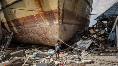 A boy stands in front of a stranded ship in Donggala on October 2.