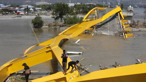 People survey the wreckage of a bridge near Talise Beach in Palu.