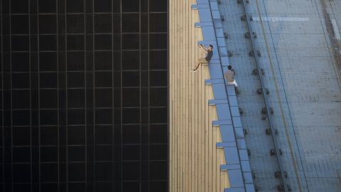 """TOPSHOT - In this photograph taken on August 23, 2016, two men take a series of selfies as they sit on the ledge of a high-rise building in an activity called """"rooftopping"""" in Hong Kong. / AFP PHOTO / Romeo GACAD / The erroneous mention[s] appearing in the metadata of this photo by ROMEO GACAD has been modified in AFP systems in the following manner: corrects byline spelling to [ROMEO GACAD] instead of [ROMMEO GACAD]. Please immediately remove the erroneous mention[s] from all your online services and delete it (them) from your servers. If you have been authorized by AFP to distribute it (them) to third parties, please ensure that the same actions are carried out by them. Failure to promptly comply with these instructions will entail liability on your part for any continued or post notification usage. Therefore we thank you very much for all your attention and prompt action. We are sorry for the inconvenience this notification may cause and remain at your disposal for any further information you may require.        (Photo credit should read ROMEO GACAD/AFP/Getty Images)"""
