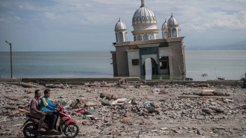 People ride a scooter past a partially submerged mosque in Palu on October 2. The mosque was knocked from its foundation during the quake and tsunami.