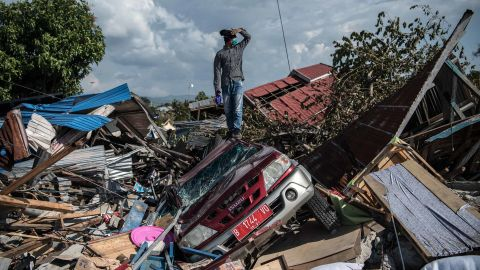 A man stands atop a car and other debris in Palu.
