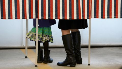 A woman is accompanied by a child inside a booth as she votes for the first US presidential primary at a fire station in Loudon, New Hampshire, on February 9, 2016.New Hampshire began voting on February 9 in the first US presidential primary with Republican Donald Trump calling on supporters to propel him to victory and Democrat Bernie Sanders primed to upstage Hillary Clinton.  The northeastern state, home to just 1.3 million people, sets the tone for the primaries and could shake out a crowded Republican field of candidates pitting Trump and arch-conservative Senator Ted Cruz against more establishment candidates led by Senator Marco Rubio. / AFP / JEWEL SAMAD        (Photo credit should read JEWEL SAMAD/AFP/Getty Images)